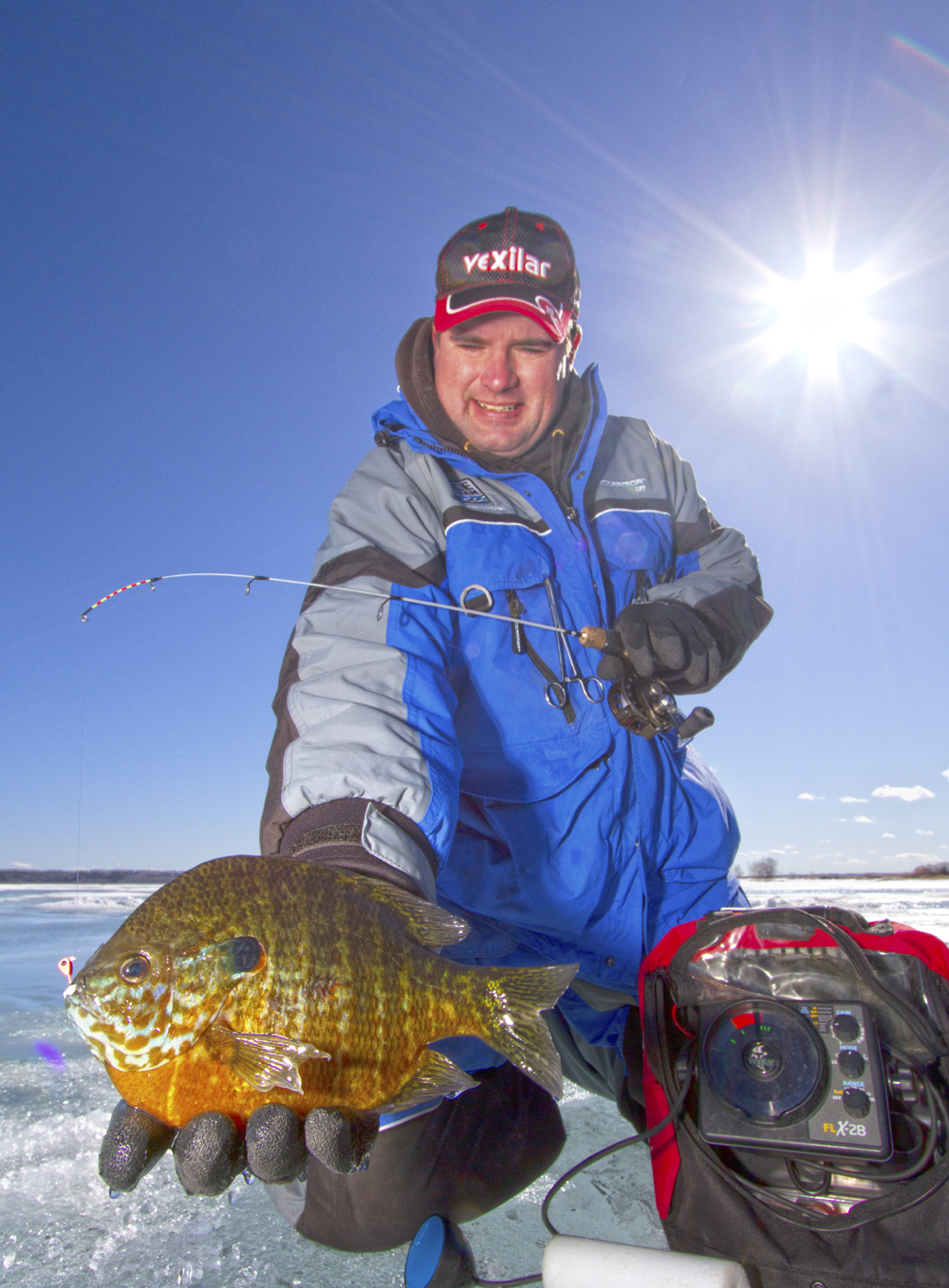 Tungsten jigs like the Dave Genz line up of Drop Jigs from Clam Pro Tackle are deadly effective but you can pick your game up even more by knowing when to incorporate additional elements of finesse. Pictured is the author Jason Mitchell with a great sunfish.